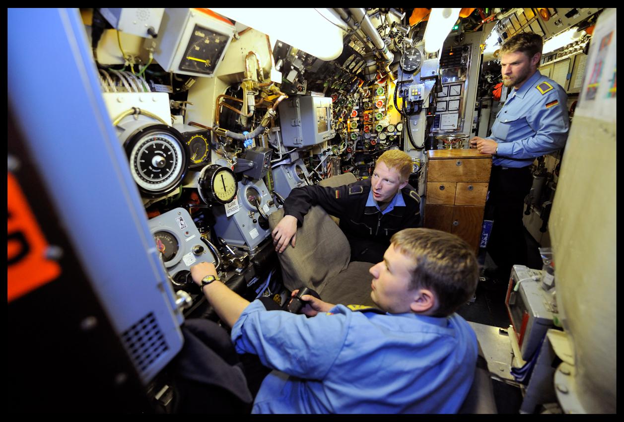 Im Herz des U-Bootes warten Offiziere und Unteroffiziere auf den Kurs und die Kommandos für sämtliche Manöver und Tauchgänge. Während der sogenannte Rudergänger (Mann rechts im Bild) die Seitenruder auf Kurs hält, beobachten die Eletronikbootsmänner die füur das Überleben an Bord wichtigen Messinstrumente. Hinter den schiffselektrischen Anlagen befindet sich der Raum für den Funker und die Steuerzentrale.