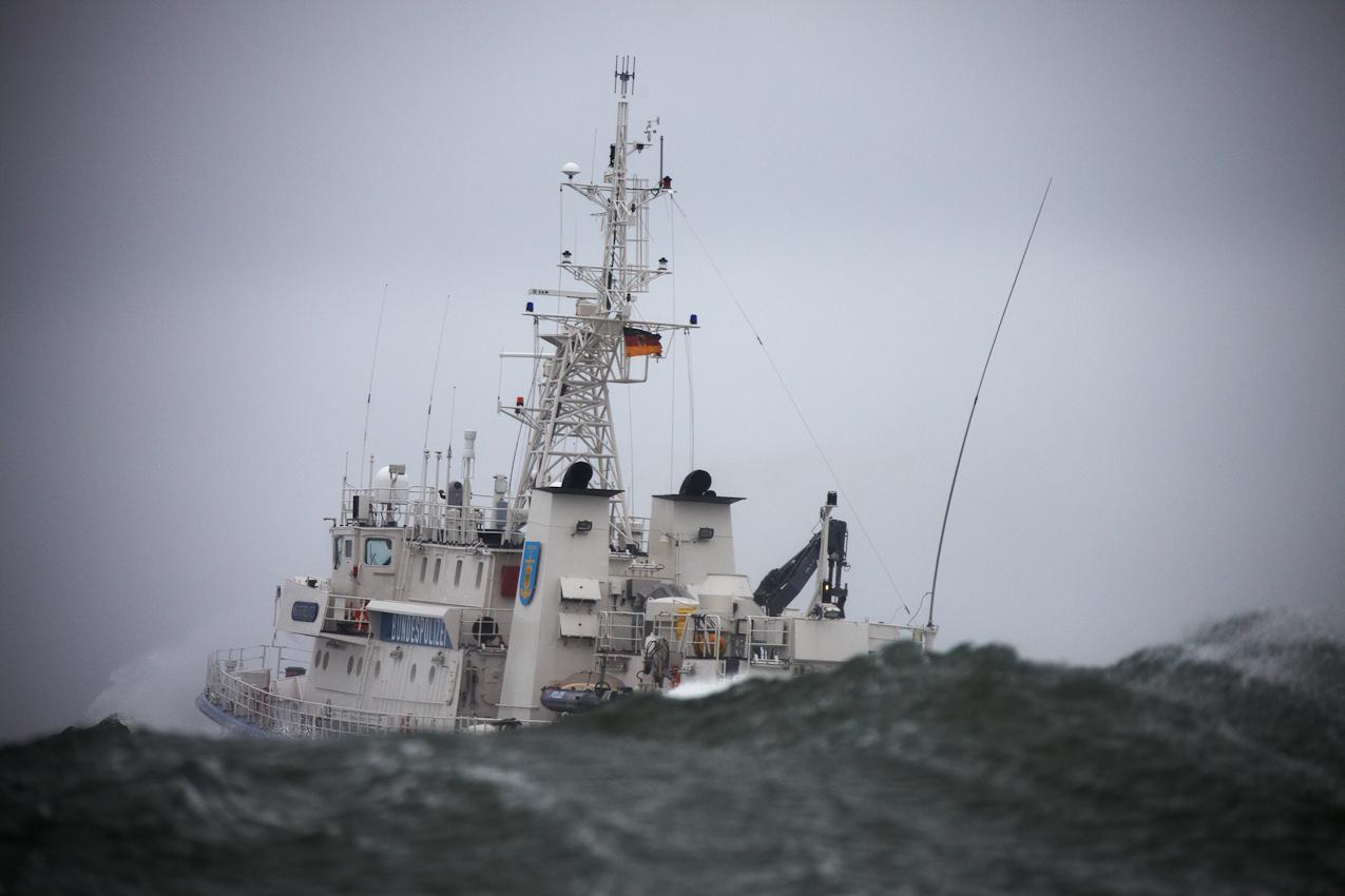 Neustadt in Holstein, Lübecker Bucht, Ostsee. 7.5.2010  --  Küstenwache im Einsatz auf der Ostsee. Die Bundespolizei ist ein Teil der deutschen Küstenwache. Das Wachboot NEUSTRELITZ der Bundespolizei läuft bei schlechtem Wetter und Windstärke 8 zu einer Routinefahrt in die Lübecker Bucht aus. Nach einer Stunde kann die Suche nach dem vermissten Surfer abgebrochen werden. Der Mann hatte sich schwimmend an Land gerettet und von dort aus die Seenotrettung informiert. Das Wachboot setzt seine Routinefahrt fort und stampft durch hohe Wellen in Richtung Fehmarnbelt.