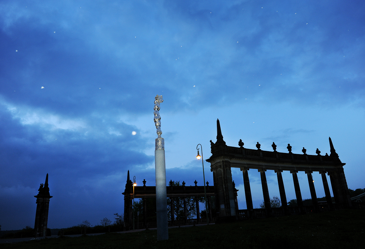 """Blick von der  Potsdamer Seite auf die Glinicker Brücke, in der Mitte die Bronzeskultptur  """"Nike 89"""" des Bildhauers Wieland Forster, die weissen Flecken im Bild sind Mücken"""