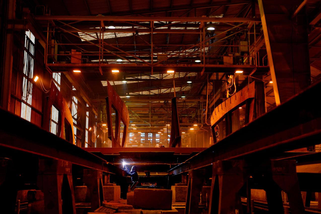"""Auf der Traditionswerft """"Flensburger Schiffbau-Gesellschaft"""" wurden seit 1872 uber 700 Schiffe gebaut. Die Werft ist mittlerweile eine der produktivsten Werften in Deutschland und hat sich auf den Bau von RoRo-Schiffen spezialisiert. Ein Schweißer arbeitet in der Vorfertigung an Stahlelementen, welche später in der Endmontage zusammengesetzt werden."""