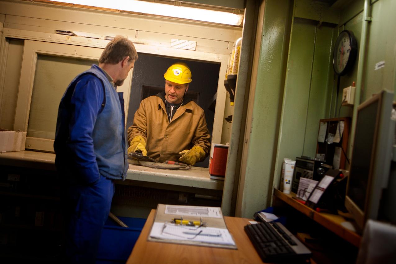 """Auf der Traditionswerft """"Flensburger Schiffbau-Gesellschaft"""" wurden seit 1872 uber 700 Schiffe gebaut. Die Werft ist mittlerweile eine der produktivsten Werften in Deutschland und hat sich auf den Bau von RoRo-Schiffen spezialisiert. Ein Werftarbeiter gibt seinen Schweißgerat zur Reperatur im Nachschublager in der großen Halle ab."""