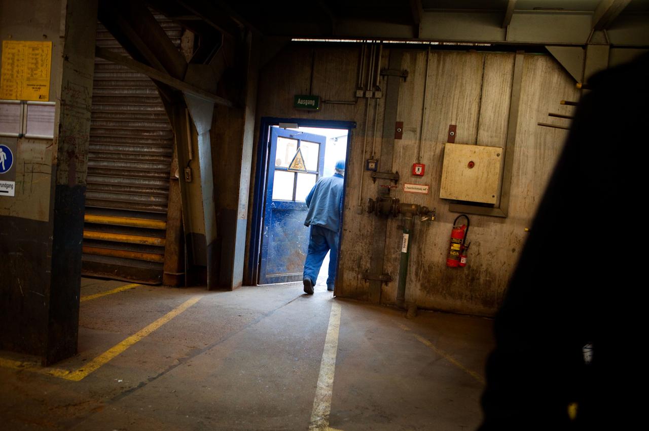 """Auf der Traditionswerft """"Flensburger Schiffbau-Gesellschaft"""" wurden seit 1872 uber 700 Schiffe gebaut. Die Werft ist mittlerweile eine der produktivsten Werften in Deutschland und hat sich auf den Bau von RoRo-Schiffen spezialisiert. Ein Werftarbeiter verlässt zur Frühstuckspause die Werfthalle."""