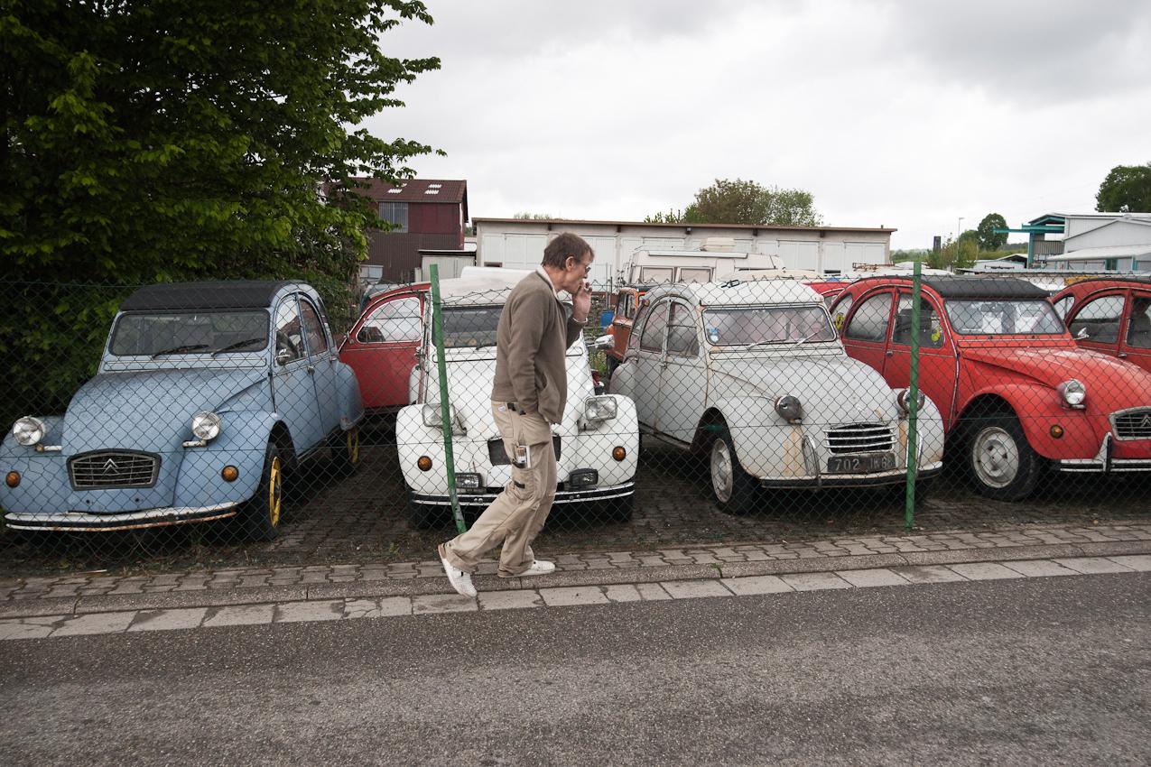 Das Foto entstand auf einer Strasse vor dem Gelaende der Auto-Werkstatt Franz Schreier 2CV Service+Teile in 74889 Sinsheim-Reihen, Baden-Wuerttemberg, Deutschland am 7. Mai 2010 um 13.29 Uhr. Zu sehen sind 2CVs (Enten) hinter einem Zaun auf dem Werkstatt-Gelaende, an denen ein Interessent rauchend vorbeilaeuft.