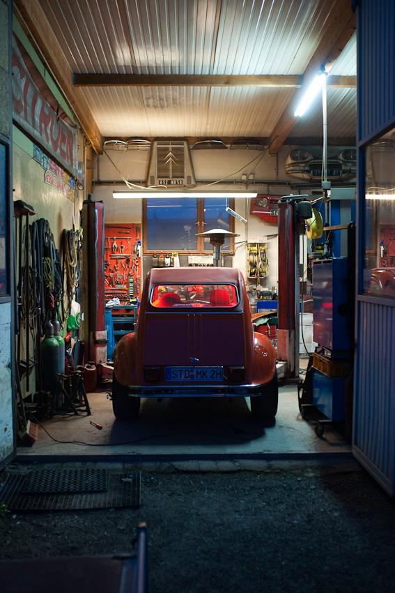 Das Foto entstand auf dem Gelaende der Auto-Werkstatt Franz Schreier 2CV Service+Teile in 74889 Sinsheim-Reihen, Baden-Wuerttemberg, Deutschland am 7. Mai 2010 um 21.22 Uhr. Zu sehen ist ein Teil der Werkstatt bei offenen Toren. Der Spezial-2CV hat eine besondere Innenbeleuchtung, an ihm schrauben der Chef Franz Schreier und sein Sohn Daniel Schreier bereits 7 Jahre im Auftrag eines Kunden.