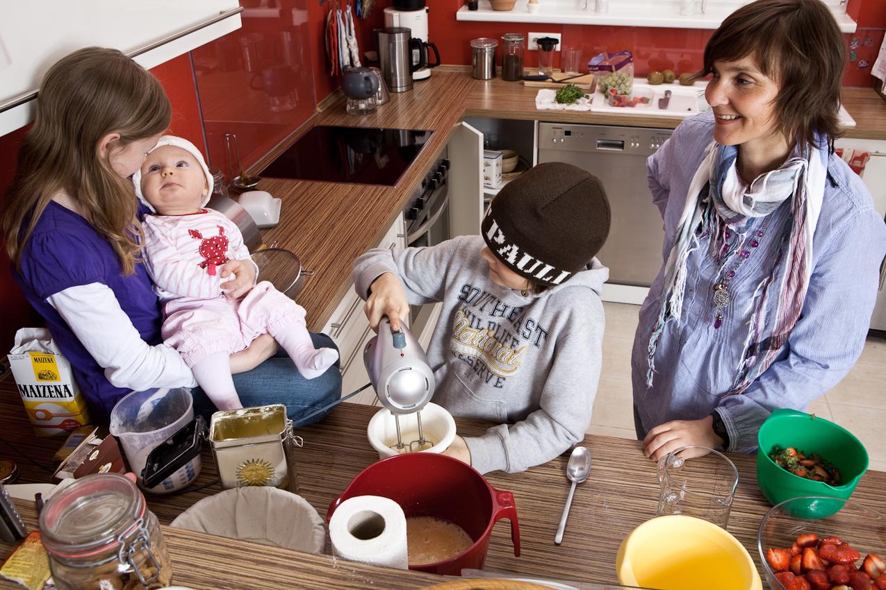 Cordula backt mit den Kindern Luca und Moritz einen Kuchen und Cara schaut zu.