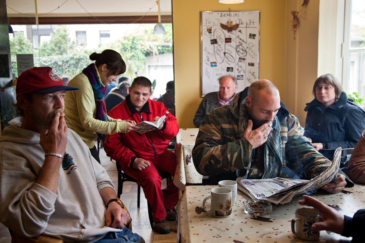 """Herford: Manni (links) kommt seit Jahren zum Tagesaufenthalt der Sozialberatungstelle. Da er immer eine Mütze trägt ist sein Spitzname """"Mütze"""". Er sitzt immer am gleichen Tisch und immer auf dem gleichen Stuhl. Projekt A: Herforder Mittagstisch e.V., Medizinische Hilfe für Bedürftige e.V., Sozialberatungsdienst. Ehrenamtliche Helfer der Herforder Petri-Gemeinde bewirten seit über 10 Jahren bedürftige Menschen jeden Tag an einem gedeckten Tisch. Im gleichen Haus sitzen auch die Profis des Sozialberatungsdienstes. Einmal die Woche bieten ehrenamtlich arbeitende  Ärztinnen Sprechstunden an."""