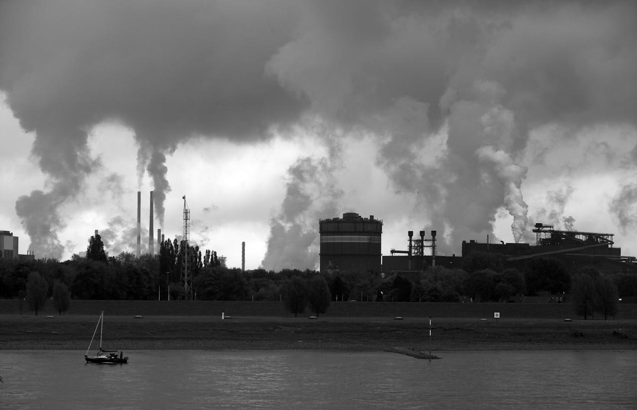 Postleitzahl 47199 Duisburg Homberg: Sicht von der Rheindeichstrasse auf den Rhein und die Silhouette der Thyssen Krupp Stahl AG in den Stadtteilen Beeckerwerth und Bruckhausen. Ein stromabwaerts fahrendes Segelboot vor der Industriekulisse.