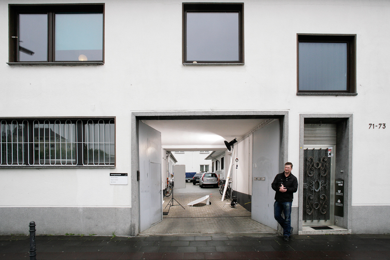"""Die Geisselstraße ist eine Wohn- und Geschäftsstraße im Kölner Stadtteil Ehrenfeld, weder schick noch heruntergekommen. Hier lebt und arbeitet eine große Bandbreite von Menschen: Millionäre, Huren, Rentner, Professoren, """"Harzer"""", Kreative und Malocher. Für """"Einen Tag Deutschland"""" habe ich den """"Status Quo Geisselstraße"""" fotografiert: Menschen, die – wie ich – auf der Geisselstraße leben und arbeiten. Making of... Wegen des Regens haben wir den Aufbau in die Toreinfahrt verlegt. Kai Funck"""