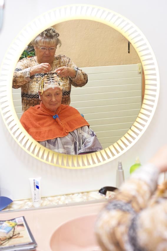 """Christa Wachowski die Chefin des Damen- und Herren- Salon ,,Die Haarsträhne"""" dreht Frau Krause, einer Stammkundin,  die Dauerwelle ein. Sie selbst hat ebenfalls Lockenwickler eingedreht.  07.05.2010, 12:10, DEU, Deutschland, NRW, Dortmund, Münsterstraße 71: Im Damen- und Herren- Salon ,,Die Haarsträhne"""" im Dortmunder Norden scheint die Zeit in den 60er Jahren stehen geblieben zu sein. In einer Zeit als der """"Pott noch kochte"""" und die Münsterstraße die Amüsiermeile des keinen Mannes war. Heute ist der Dortmunder Norden ein Stadtteil mit hoher Arbeitslosigkeit, hohem Migrantenanteil und hohem Ladenleerstand."""