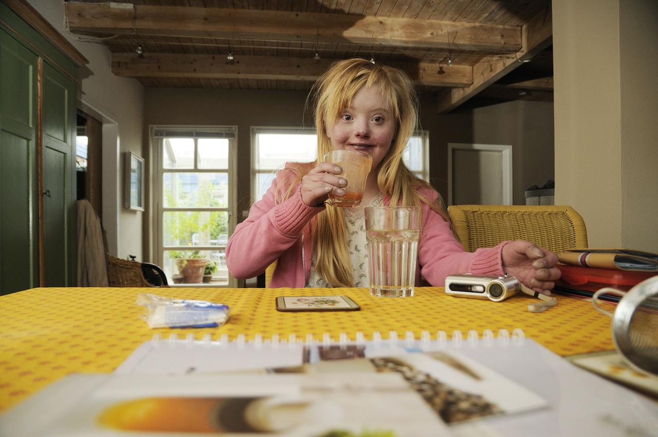 Keke, eine junge Frau, 18 Jahre, lebt mit dem Down-Syndrom (Trisomie 21). Die Familie versucht ein normales Leben zu führen. Keke ist meist gut drauf, selten erlebt man sie traurig oder verzagt. Sie nimmt das Leben wie es ist. Auf dem Foto zeigt sie beim Frühstück, danach geht es zur Schule.