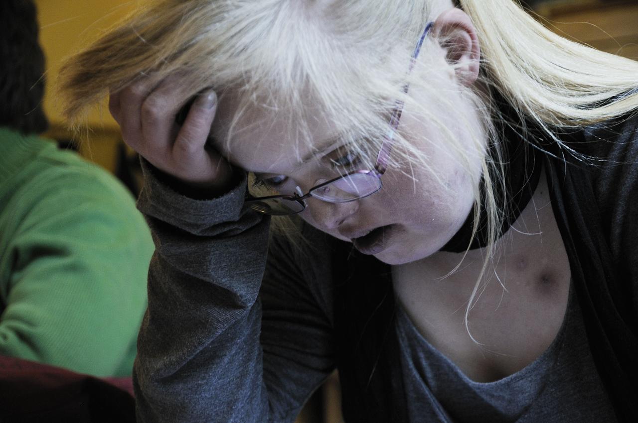 Keke, eine junge Frau, 18 Jahre, lebt mit dem Down-Syndrom (Trisomie 21). Die Familie versucht ein normales Leben zu fuehren. Keke ist meist gut drauf, selten erlebt man sie traurig oder verzagt. Sie nimmt das Leben wie es ist. Auf dem Foto ist sie in der Schule. Sie kann lesen, rechnen und schreiben.