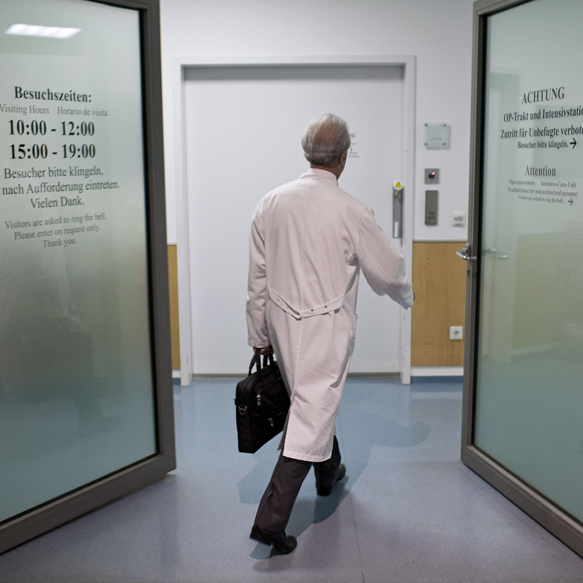 Neuchirurgischer Eingriff am offenen Gehirn, Prof. Samii vom INI Hannover. Prof. Samii auf dem Weg zu einem der insgesamt sechs OP-Räume der INI-Klinik. Für meine Reportage begleite ich für ein paar Stunden den heute 72-jährigen Neuchirurgen Prof. Dr. Madjid Samii. Der gebürtige Iraner ist seit über 45 Jahren auf dem Gebiet der Neurochirurgie tätig und einer der führenden Neurochirurgen. Das von ihm gegründete International Neuroscience Institute (INI) in Hannover ist eine der modernsten Neurokliniken der Welt.  In seiner ersten Operation am Vormittag des 7. Mai entfernte Prof. Samii und ein 8-köpfiges Team einer Frau einen Tumor aus dem Gehirn. Um den Tumor möglichst radikal aber schonend entfernen zu können, wurde das Gehirn der Patientin zuvor in einem Kernspintomographen vermessen. Die so mit modernster Neuronavigation durchgeführte Operation verlangte über Stunden absolute Konzentration und Präzision. Die freistehende Arbeit erfordert nicht nur geistige sondern auch absolute körperliche Fitness.