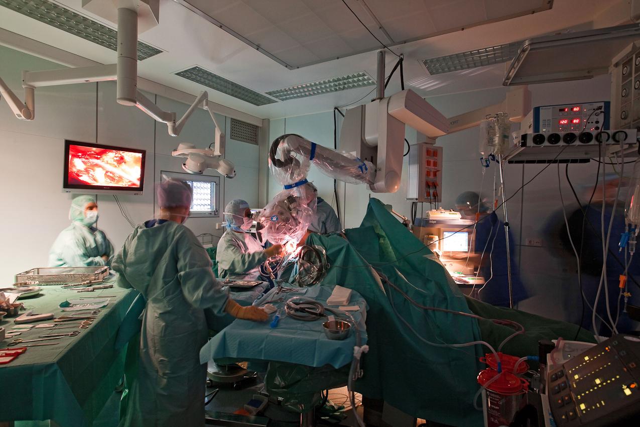 Neuchirurgischer Eingriff am offenen Gehirn, Prof. Samii vom INI Hannover.  Das Bild, das Prof. Samii über sein hochauflösendes Mikroskop sieht, wird live auf mehrere Bildschirme übertragen. Die geistige und körperliche Konzentration des Operateurs überträgt sich auf das ganze Team. Es wird kaum gesprochen.  Während der OP wurde das Raumlicht gedimmt.  Für meine Reportage begleite ich für ein paar Stunden den heute 72-jährigen Neuchirurgen Prof. Dr. Madjid Samii. Der gebürtige Iraner ist seit über 45 Jahren auf dem Gebiet der Neurochirurgie tätig und einer der führenden Neurochirurgen. Das von ihm gegründete International Neuroscience Institute (INI) in Hannover ist eine der modernsten Neurokliniken der Welt.  In seiner ersten Operation am Vormittag des 7. Mai entfernte Prof. Samii und ein 8-köpfiges Team einer Frau einen Tumor aus dem Gehirn. Um den Tumor möglichst radikal aber schonend entfernen zu können, wurde das Gehirn der Patientin zuvor in einem Kernspintomographen vermessen. Die so mit modernster Neuronavigation durchgeführte Operation verlangte über Stunden absolute Konzentration und Präzision. Die freistehende Arbeit erfordert nicht nur geistige sondern auch absolute körperliche Fitness.