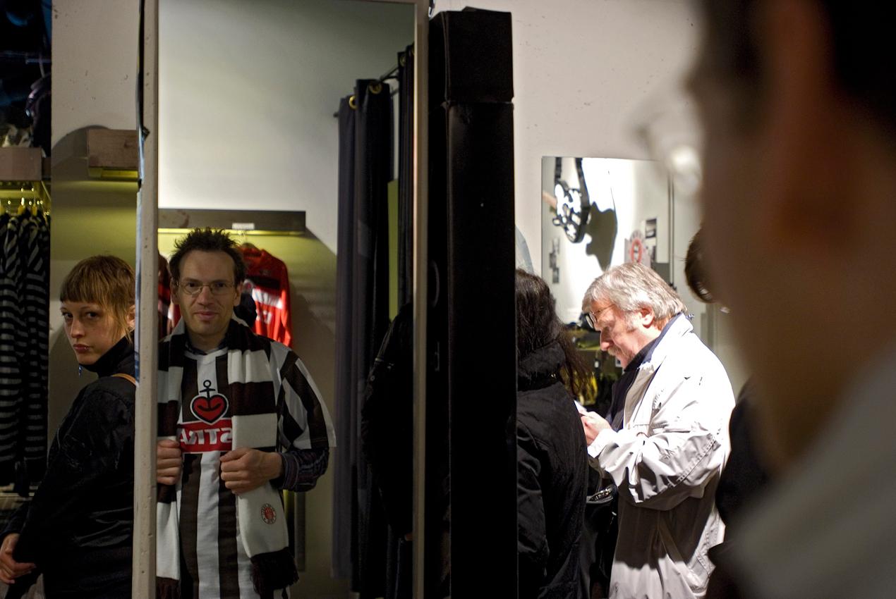 Der St. Pauli-Fan Thomas betrachtet sich in seinem neuen Tricot im Spiegel im Fanshop des FC St. Pauli, das er für die  Aufstiegsparty in die Bundesliga  am Sonntag kauft.