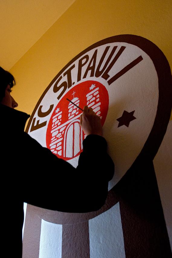 Die scheue, angehende Kunststudentin Marie-Luisa vollendet am Nachmittag des 7. Mai mit viel Liebe zum Detail  ihre Wandmalerei des FC St. Pauli-Logos. Die Basiskneipe Tippel II, Seilerstr. Ecke Hain-Hoyer-Str., beauftragte sie den Eingangsbereich zur100-Jahrfeier des Vereins mit dem Logo zu schmücken.