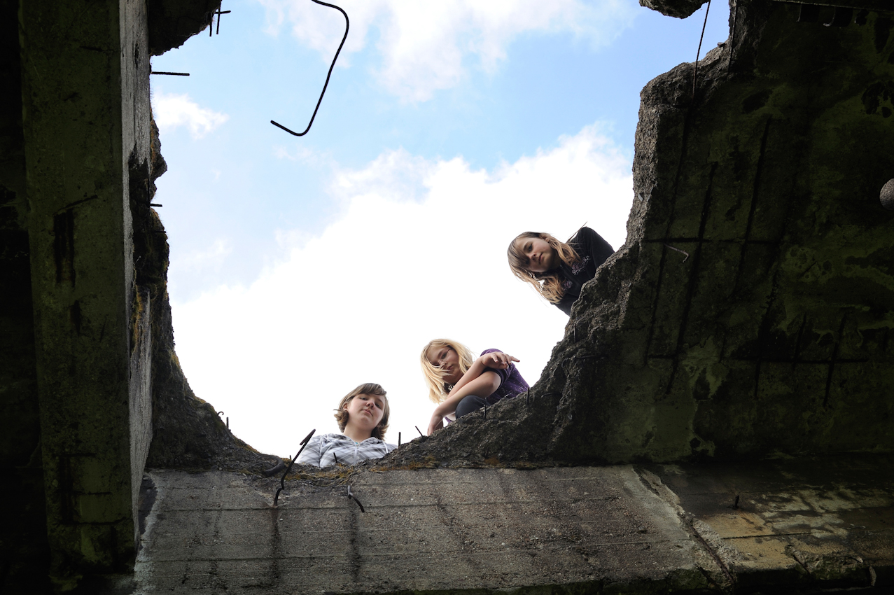 """Isabelle Buder, Conny Kaiser und Nicole Schmidt schauen durch ein Loch der im 2.Weltkrieg zerstorten """"Langen Brücke"""" am westlichen Ufer der Neiße."""