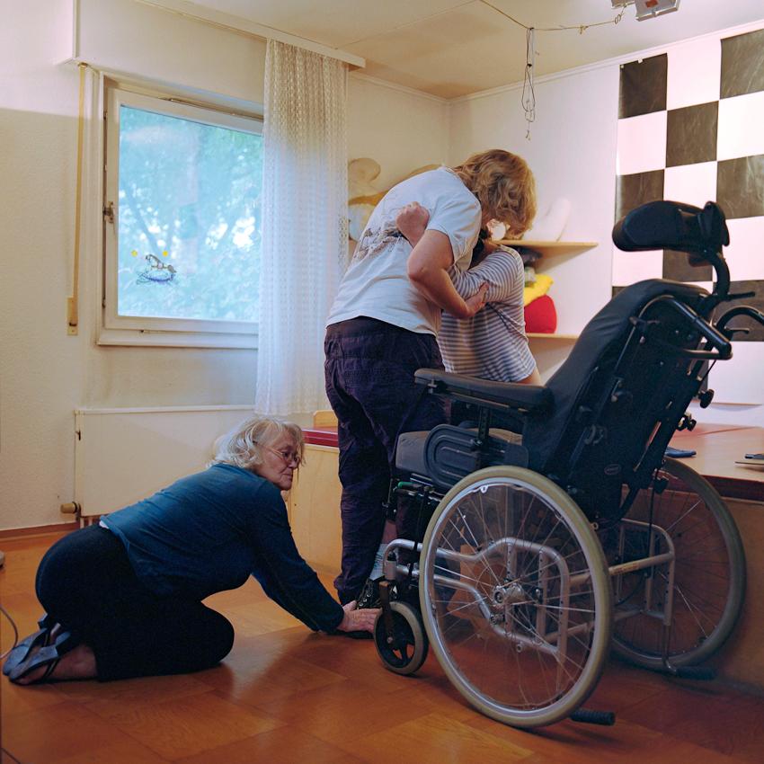 Mutter Helga hält am 07.05.2010 die Füße ihrer Tochter Svenja fest, während die Physiotherapeutin Kirsten Bejarano Svenja in den Rollstuhl setzt. Im Wachkoma kommt es aufgrund einer Schädigung zwischen Stammhirn und Großhirn zu Bewusstseins- und Wahrnehmungsstörungen. Umso wichtiger ist der sensible Umgang der Betreuenden mit den Betroffenen. Die heute 42-jährige Svenja fiel 1992 durch einen Reitunfall in Mexiko ins Wachkoma. Sie lebt bei iher Mutter in Hannover.