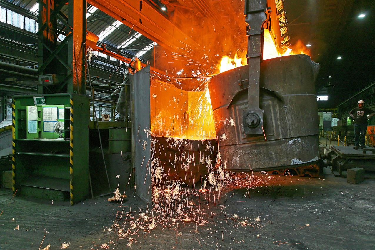 Bevor das 30 Tonnen Roheisen zur Gussform fuer ein Pumpengehaeuse befoerdert wird muss der Giessereimeister erneut die unsaubere Oberflaeche von Schlackeresten und Ablagerungen mit einem Schaber entfernen. Zu der Zeit betraegt die Temperatur des Roheisens in der Pfanne 1375 Grad. Dies entspricht auch der Temperatur fuer den eigentlichen Giessvorgang. Das Verfahren in dieser Eisengiesserei wird seit ca. 160 Jahren fast unveraendert fortgefuehrt. Noch heute ist diese Eisengiesserei ein Unternehmen mit kontinuierlichem Absatz. Die Eisengussprodukte dienen meist als Gehaeuse fuer grosse Turbinenanlagen, Kokillen oder Gehaeuse von Schiffsmotoren. Eisenguss in der Eisengiesserei der Friedrich - Wilhelms- Huette in Muelheim / Ruhr