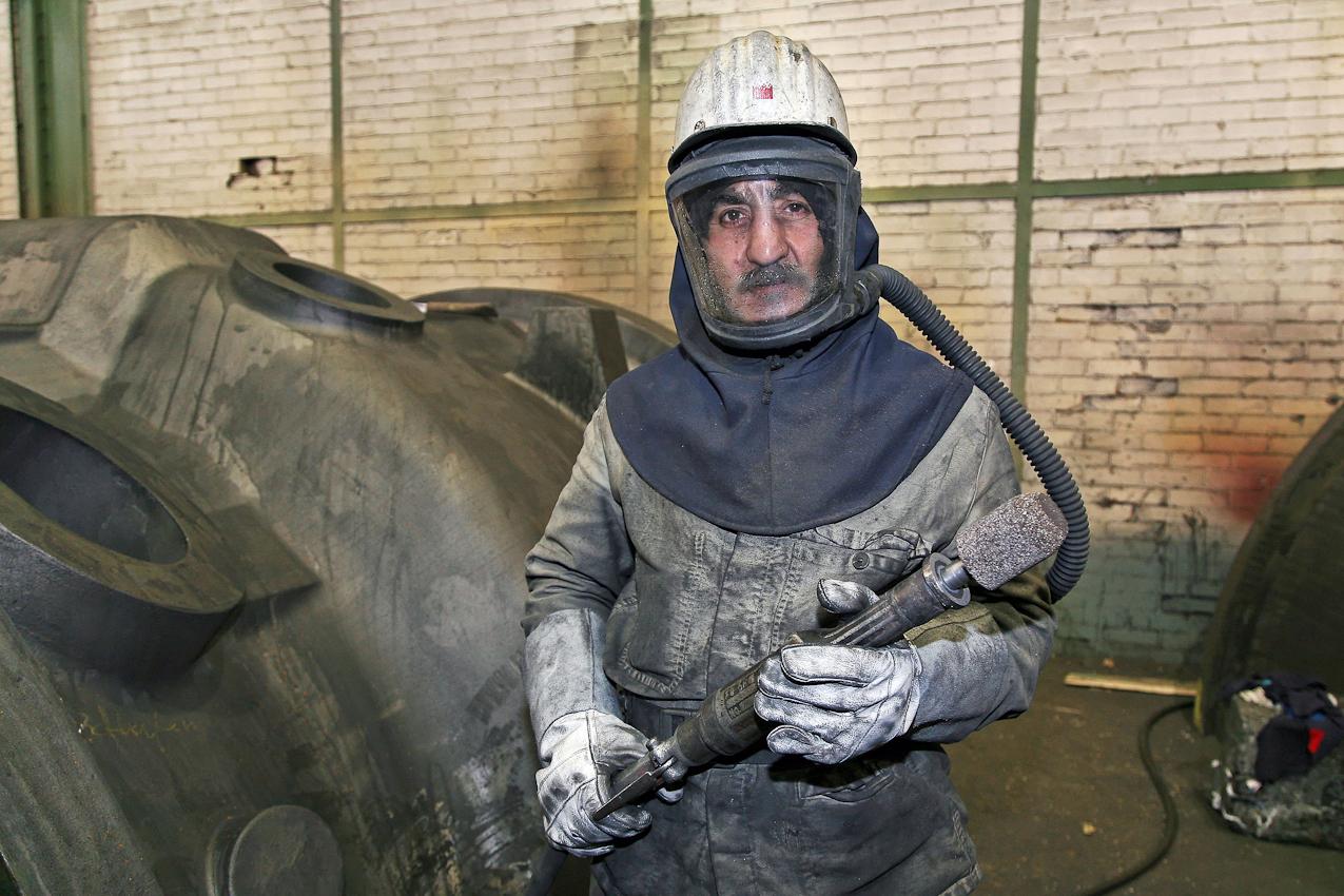 Das fast fertige Pumpengehaeuse wird einem letzten Schliff in der Versandhalle unterzogen. Ueberschuessige Grate und Unebenheiten werden entfernt. Der tuerkische Arbeiter Murat Guelen muss unter einer beatmeten Vollmaske Schwerstarbeit verrichten. Portrait. Das Verfahren in dieser Eisengiesserei wird seit ca. 160 Jahren fast unveraendert fortgefuehrt. Noch heute ist diese Eisengiesserei ein Unternehmen mit kontinuierlichem Absatz. Die Eisengussprodukte dienen meist als Gehaeuse fuer grosse Turbinenanlagen, Kokillen oder Gehaeuse von Schiffsmotoren. Eisenguss in der Eisengiesserei der Friedrich - Wilhelms- Huette in Muelheim / Ruhr