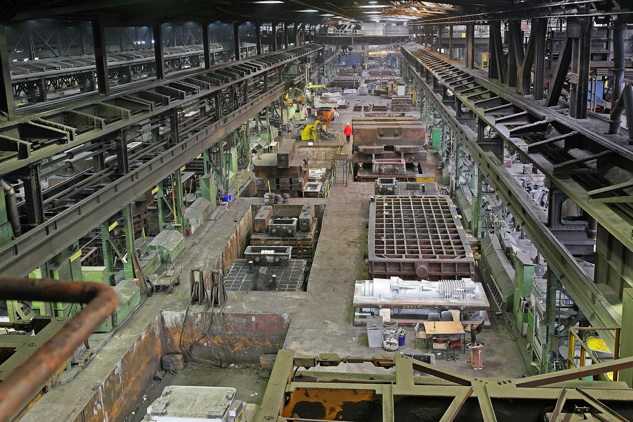 Halle der Eisengiesserei. Einblick in die Produktion. Im Boden sind schon Formen fuer den Eisenguss eingelassen und vorbereitet. In solchen Produktionshallen hat sich von der Logistik in den vergangenen 50 Jahren nichts veraendert. Dennoch wird in 2 Schichten trotz Krise gearbeitet. Das Verfahren in dieser Eisengiesserei wird seit ca. 160 Jahren fast unveraendert fortgefuehrt. Noch heute ist diese Eisengiesserei ein Unternehmen mit kontinuierlichem Absatz. Die Eisengussprodukte dienen meist als Gehaeuse fuer grosse Turbinenanlagen, Kokillen oder Gehaeuse von Schiffsmotoren. Eisenguss in der Eisengiesserei der Friedrich - Wilhelms- Huette in Muelheim / Ruhr