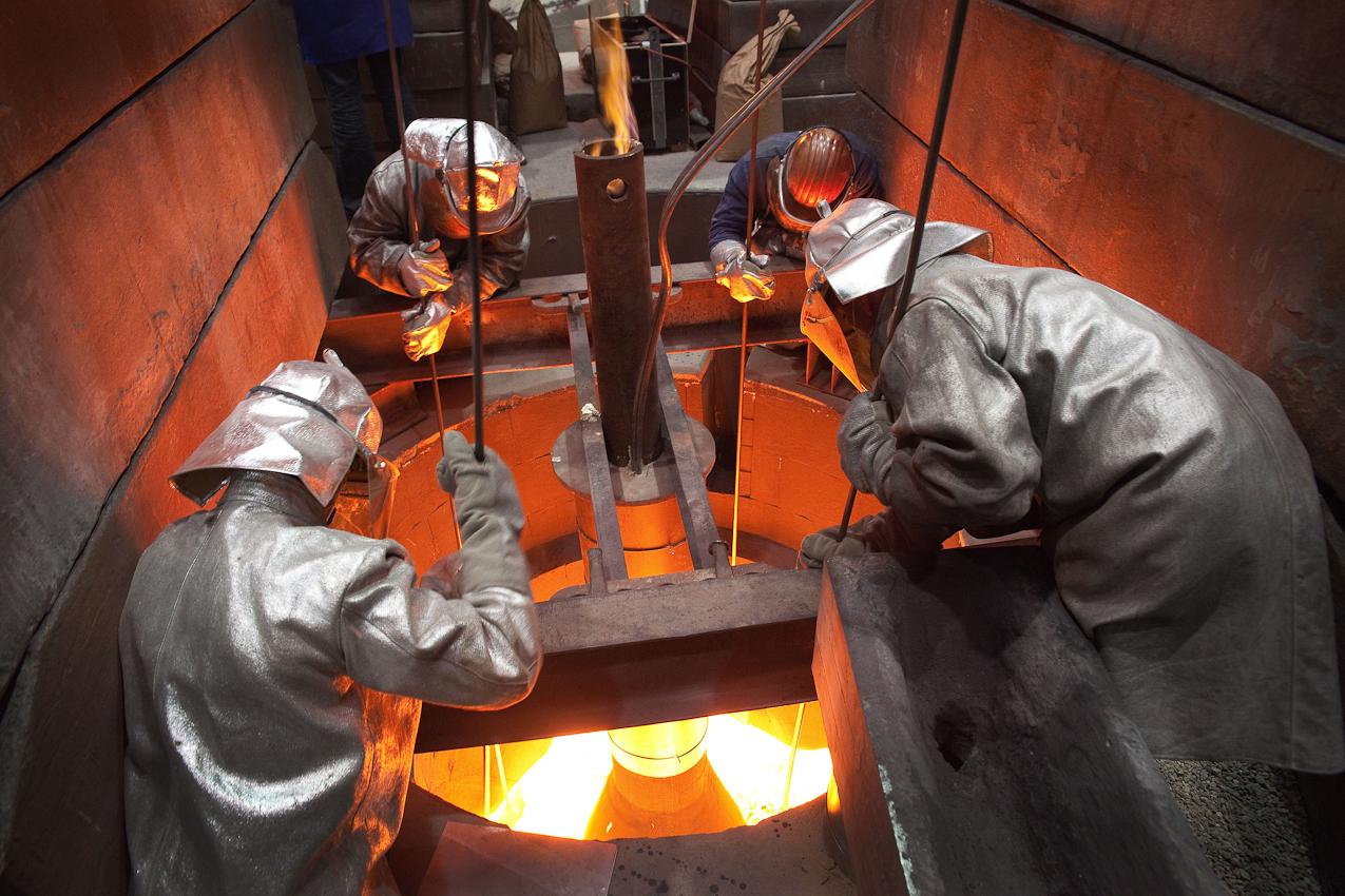Arbeiter in Schutzanzügen beobachten den Gussvorgang durch eine Öffnung in der Gussform.