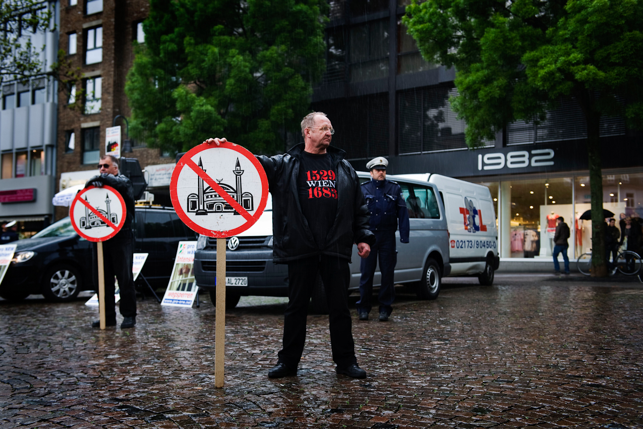 Mitglieder der Partei pro-NRW stehen mit Schildern von einer durchgestrichenen Moschee auf dem Markt vor dem Rathaus in Aachen.