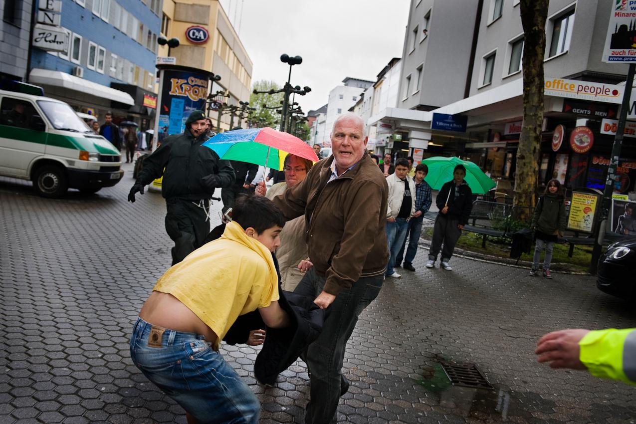 Der Parteifunktionär Ronald Micklich der Partei pro-NRW attackiert in Düren auf dem Kaiserplatz einen Jungen, der versucht hat, die Wahlveranstaltung zu stören.