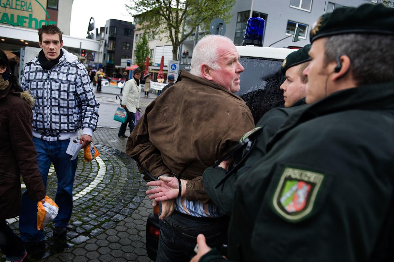 Polizisten führen Ronald Micklich von der Partei pro-NRW mit Handfesseln ab. Der Parteifunktionär hat einen Jungen attackiert, der versuchte, eine Wahlveranstaltung der Partei pro-NRW zu stören.