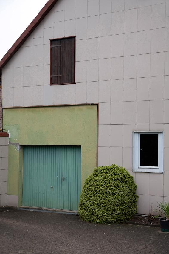 Weserbergland, Eschershausen, Steinweg, 9:45 Uhr. Kunststoffbehängte Giebelfassade mit halbem, akkurat gestutztem Buchsbaum.