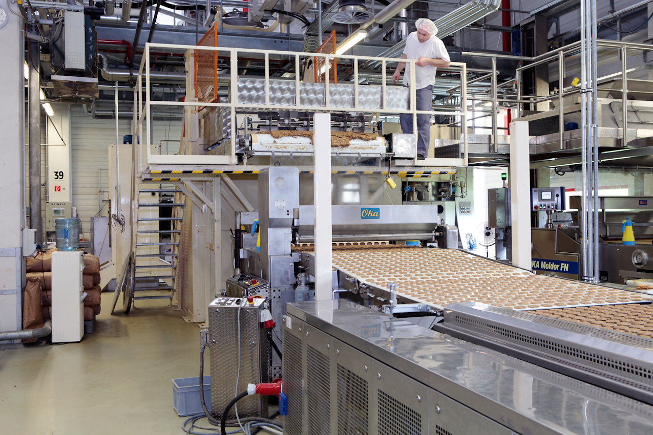 Ein Bandarbeiter beobachtet eine Produktion von Keksen.