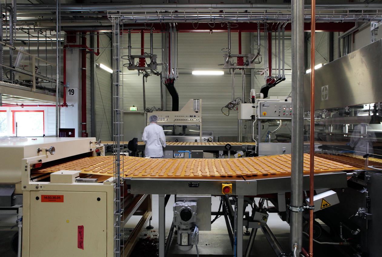 Bandarbeiterin am Fließband. Im Vordergrund ebenfalls ein Förderband mit einer Keksproduktion.