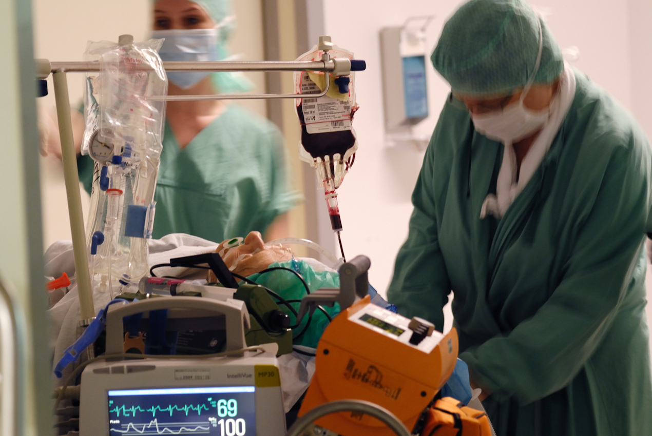 Der Patient erwacht nach der Operation aus der Vollnarkose. Eine Blutkonserve gleicht seinen Blutverlust während der Operation aus. Das OP-Personal überwacht die lebenswichtigen Funktionen.