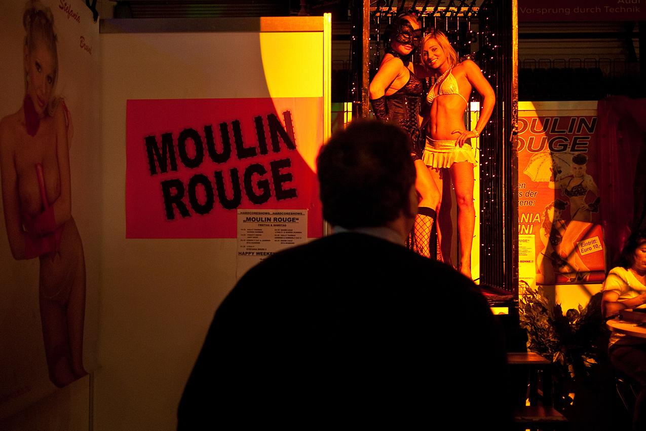 """Bevor die Damen sich im """"Moulin Rouge"""" vor dem zahlenden Publikum entblättern, präsentieren sie sich den Messebesuchern in diesem Käfig."""