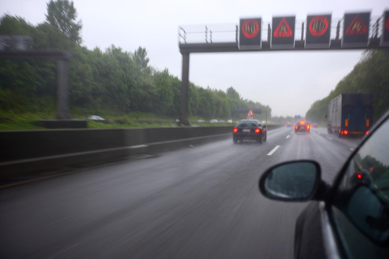 Ein Tag Deutschland, auf der Autobahn A40, Ruhrschnellweg. Regen, Morgens, zwanzig nach Sechs. Die Warnschilder kuendigen den kommenden Stau an. Baustelle bei Gelsenkirchen-SYd. Abbremsen, Schleichfahrt für 5 Kilometer. Alltag für Pendler auf der A40. Essen, Deutschland.