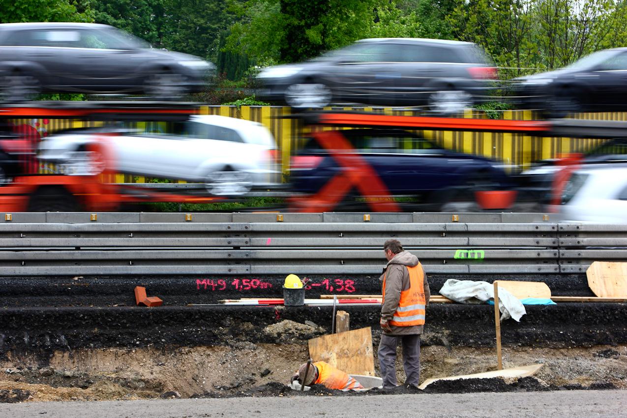 Ein Tag Deutschland, auf der Autobahn A40, Ruhrschnellweg. Ausbau der A40 von 4 auf 6 Spuren. In Bochum arbeiten zwei Bauarbeiter einen Meter neben der Leitplanke in der Baustelle an der neuen Kanalisation fuer die Autobahn. Bochum, NRW, Deutschland