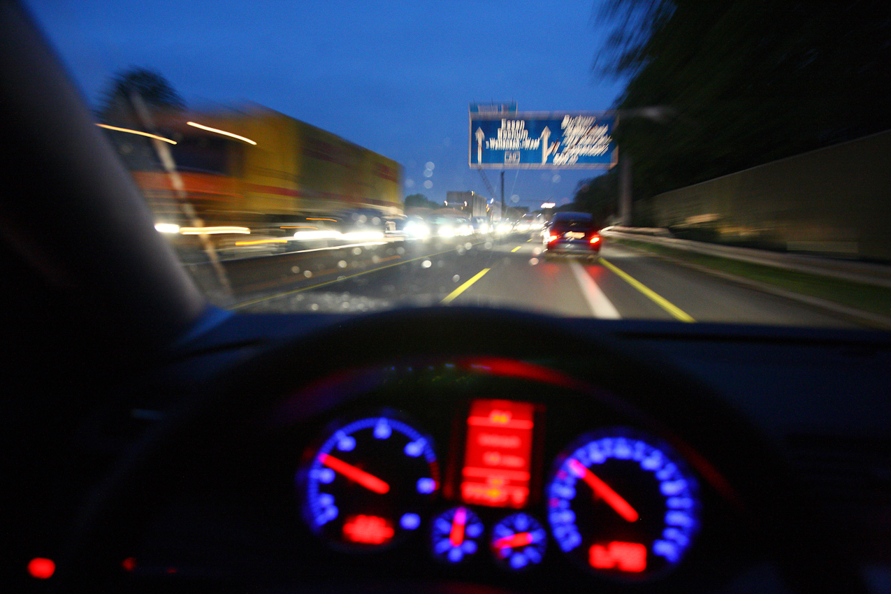 Ein Tag Deutschland, auf der Autobahn A40, Ruhrschnellweg. Heimfahrt. Die Spur nach Westen ist frei. Doch Richtung Osten, nach Dortmund, staut sich der Verkehr zur spaeten Stunde noch auf Grund einer Nachtbaustelle. Der Verkehrsfunk bringt den Stau noch bis weit nach Mitternacht im Radio. Bochum, NRW, Deutschland