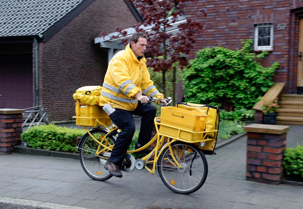 Werne a.d. Lippe, DEU, 07.05.10 - Der Briefzusteller Dirk Leinberger ist am Freitag, 7. Mai 2010, in Werne an der Lippe bei regnerischem Wetter mit seinem Fahrrad unterwegs.