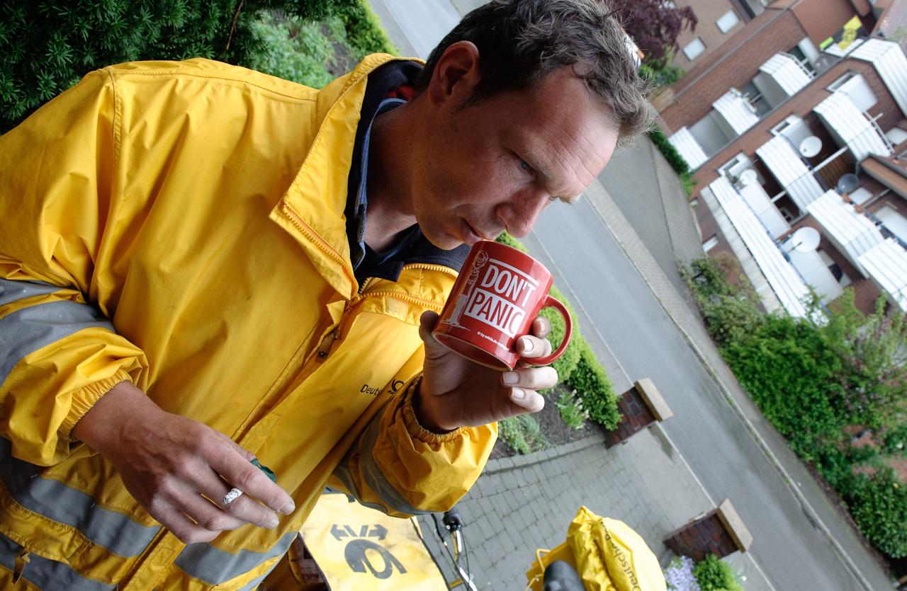 Werne a.d. Lippe, DEU, 07.05.10 - Der Briefzusteller Dirk Leinberger macht am Freitag, 7. Mai 2010, in Werne an der Lippe bei regnerischem Wetter eine Kaffeepause.