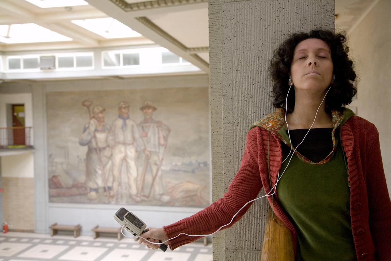 """Samirah A-Amrie von """"Musik im Turm"""" wird von der Fotografin Edda Treuberg in der Lohn- und Lichthalle der ehemaligen Zeche Lohberg für """"Ein Tag Deutschland"""" portraitiert. Die Musikerin, die in ihren Arbeitsräumen im Kreativ.Quartier Lohberg auch Gesangsunterricht gibt und komponiert, ist vielseitig ausgebildet und mit Preisen ausgezeichnet. Sie gibt Konzerte und komponiert Filmmusik. Hier nimmt sie """"Zechentöne"""" auf für ein neues Projekt. Über ihre Arbeit sagt sie: """"Ich bin Musikerin. Das bin ich einfach. Ich bin kreativ, weil es aus mir kommt oder auch in der Zusammenarbeit oder im Zusammenspiel mit anderen entsteht. Manchmal, so wie hier, nehme ich Geräusche auf, lasse ich mich von ihnen inspirieren und greife sie dann in meinen Kompositionen wieder auf. Das Komponieren bringt das """"etwas schaffen wollen"""" in mir zum Ausdruck, das Singen das """"etwas sagen/ geben wollen"""" und das Unterrichten das """"unterstützen wollen"""". Drei schöne Komponenten, die meinen Job ausmachen."""""""