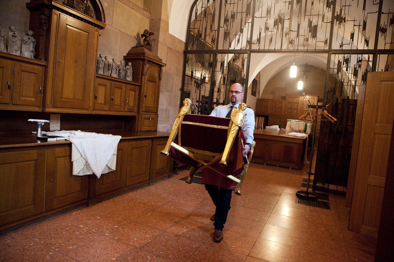 """Am Nachmittag des 7. Mai 2010 bringt Domküster Frank Wiegand in Vorbereitung des Abendlobs das Faldistorium aus der Sakristei des Mainzer Doms. Das Faldistorium, auch """"Thron"""" genannt, ist ein liturgisches Möbelstück und wird hier für Kardinal Karl Lehmann, Bischof von Mainz, bereitgestellt."""