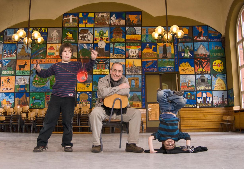 Später Vater Jose Giribas aus Chile mit seinen Söhnen Alejandro (l.) und Danillo in der Aula der deutsch-spanischen Grundschule Joan Miro in Berlin-Charlottenburg. Die Kinder wollen ihrem Vater vor dem Nachhausegehen noch ihre Kunststücke zeigen.