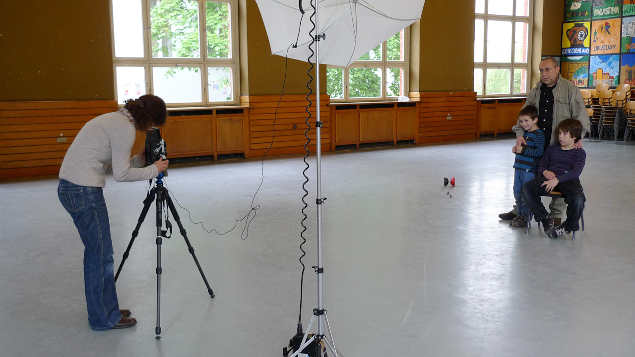 Berlin, DEU, 07.05.2010: Fotografin Anna Weise mit Jose Giribas aus Chile mit seinen Soehnen Alejandro (li) und Danillo (re) in der Aula der deutsch-spanischen Grundschule Joan Miro in Charlottenburg.