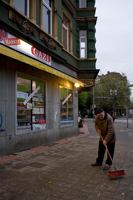Vor dem türkischen Lebensmittelladen Dagdelen Market in Hannover fegt der Vater des Inhabers den Gehweg. Nach elf Stunden Arbeit beginnt hier bald der Feierabend.