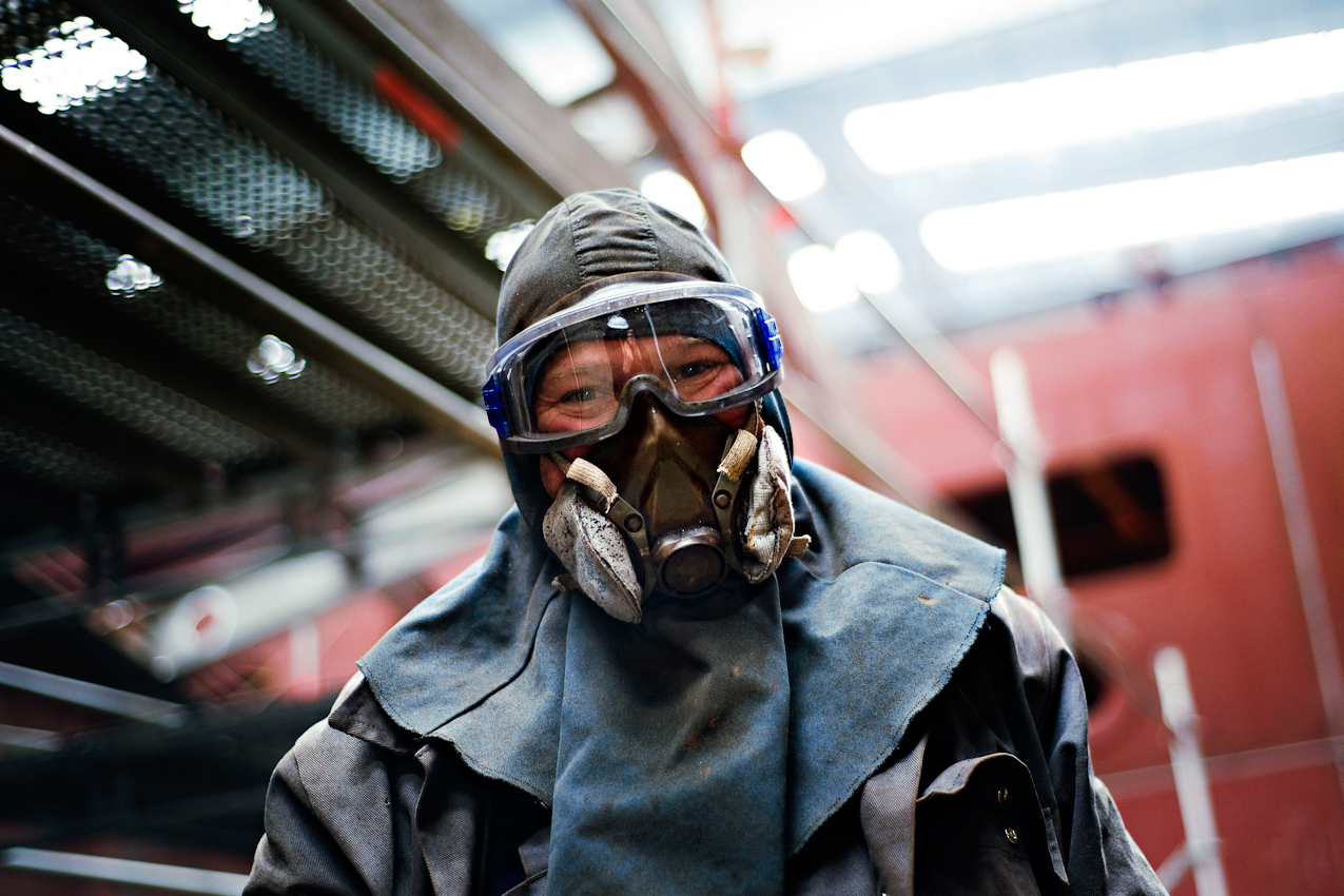 Ein Stahlarbeiter, der mit einer Flex im Vollschutz in der Dockhalle 1 der Meyer Werft arbeitet.