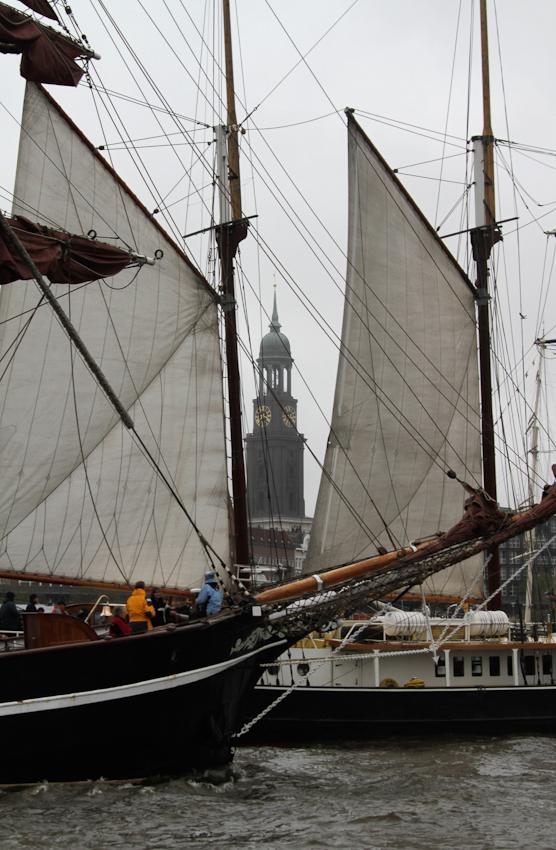 """Segelschiffe beim Hamburger Hafengeburtstag am 7. Mai 2010 in den Hafen einlaufend. Im Hintergrund ist Hamburgs Wahrzeichen, der """"Michel"""" ."""