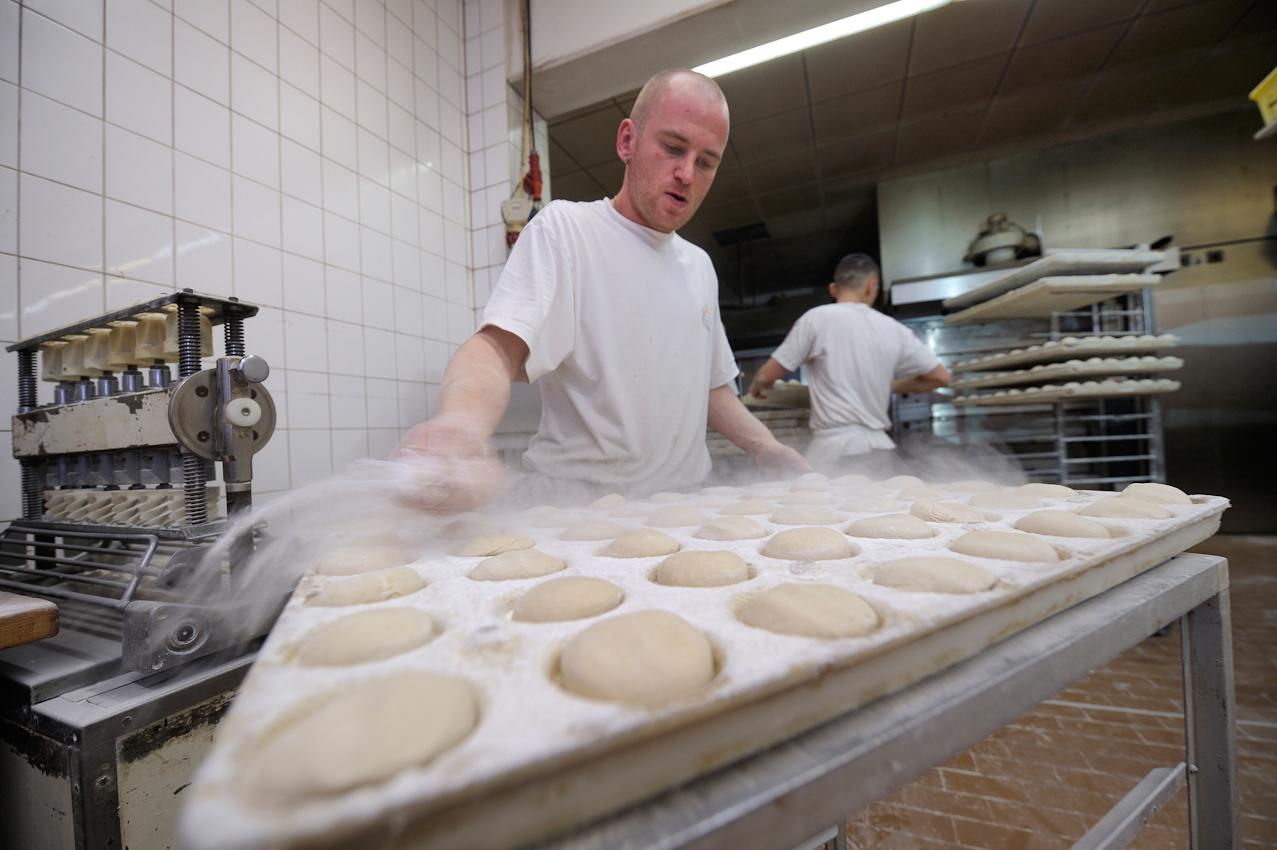 Heßheim, Stadtbäckerei Frankenthal. Brotchenproduktion. Lars Walk bestreut Teiglinge mit Mehl, damit diese nicht in der Formmaschine (ganz links) kleben bleiben.