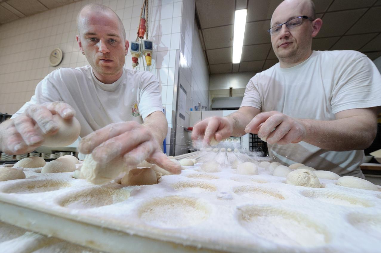 Heßheim, Stadtbäckerei Frankenthal. Brotchenproduktion. V. l. Lars Walk und Harald Heiss (Produktionsleiter) nehmen die Teiglinge vom Teigteiler ab und setzen diese in Kuhlenkasten fur die Weiterverarbeitung zu Kaiserbrötchen