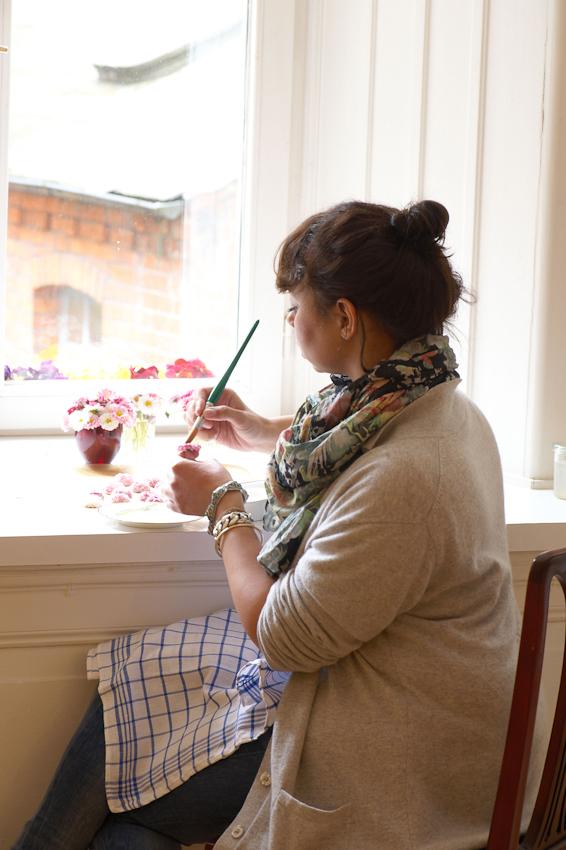 """Die Blüten, die in der Firma """"Evers & Tochter Manufaktur"""" verarbeitet werden, stammen ausschließlich aus dem eigenen Garten und den Garten von Verwandten und Freunden aus der Nachbarschaft. Sie werden frisch geerntet und sofort verarbeitet, zunächst werden sie mit einer Mischung aus Gummiarabicum und Alkohol eingepinselt, dann mit Zucker berieselt und zum Trocknen ausgelegt. Blüten, die nicht sofort verarbeitet werden können, wandern zum kühlen in den Fensterzwischenraum des alten Lübecker Kaufmannshauses"""