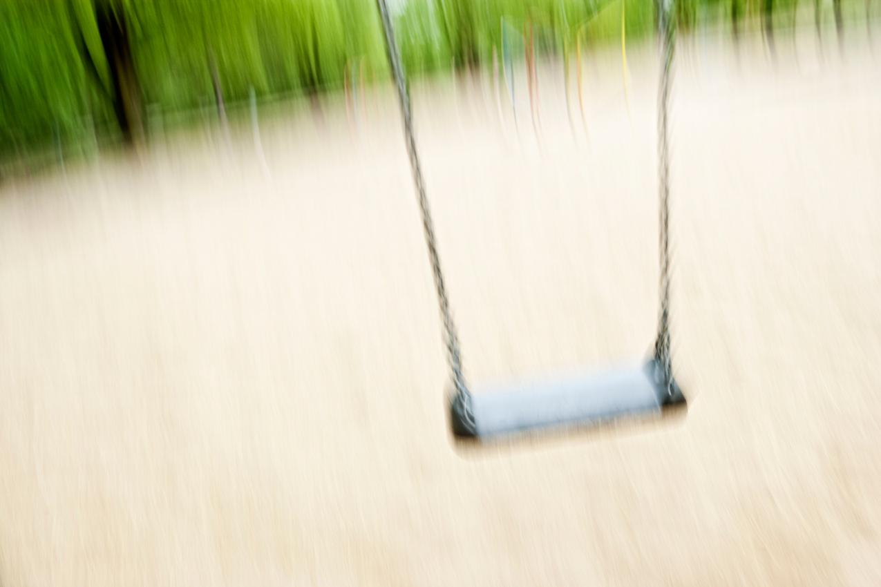 Beobachtung der Erkundung des maritimen Kinderspielplatz im Stadtpark Hamburg/Winterhude durch ein Kleinkind. Eine in Bewegung befindene Schaukel vor verschwommenen Hintergrund. Die Aufnahme wurde am 7.5.2010 um 16:29h gemacht.