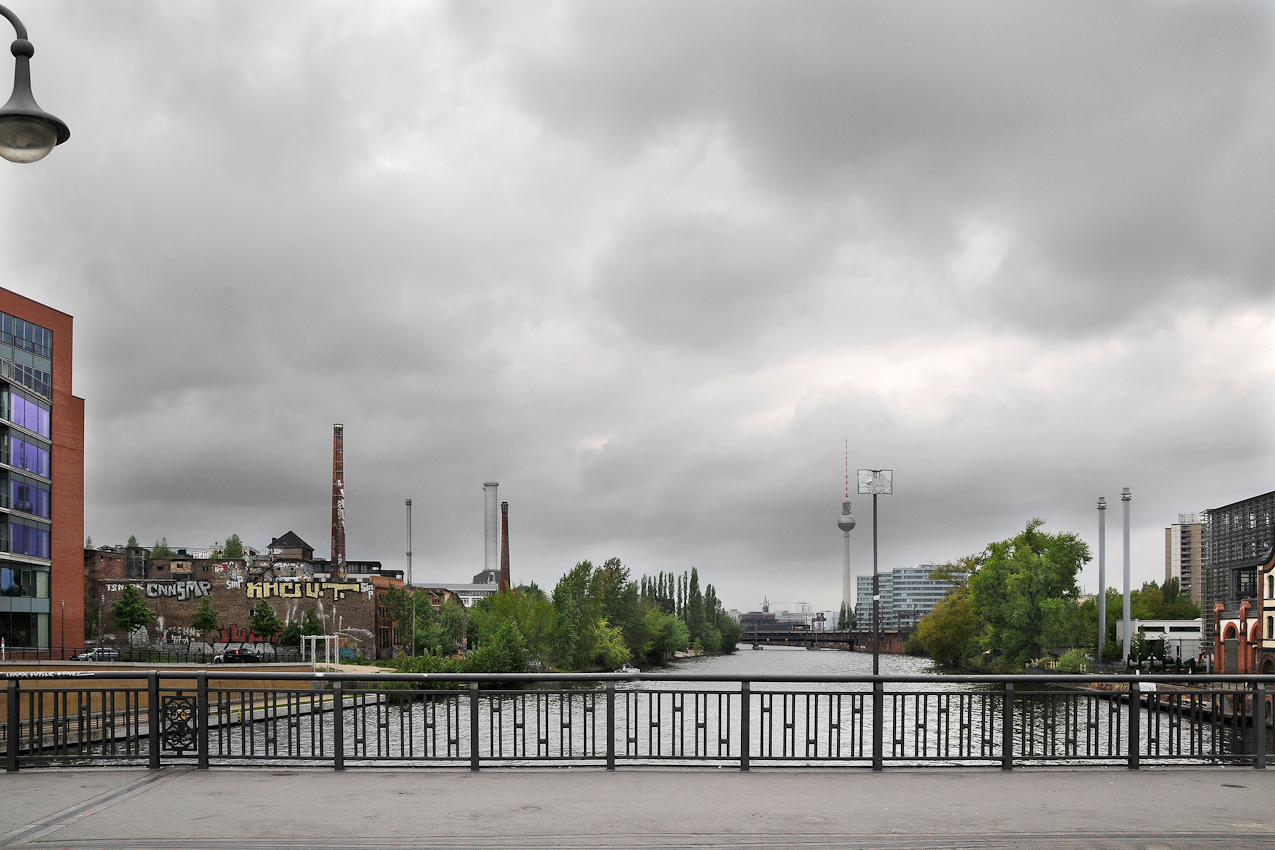Blick von der Schillingbrücke in westliche Richtung über die Spree zum Berliner Fernsehturm. Der Maihimmel wird durch dichte graue Wolken beherrscht. Links am Bildrand sieht man im Anschnitt den Verwaltungsneubau der Vereinten Dienstleistungsgewerkschaft ver.di. Daneben, ebenfalls direkt am Spreeufer, liegen die denkmalgeschützten Anlagen der seit den 1990er Jahren ungenutzten ehemaligen Eisfabrik Berlin Mitte, zu erkennen am hohen Ziegelschornstein, der Maschinenhalle mit spitzer Turmhaube und zahlreichen Graffiti an der langen Brandwand zum leer geräumten Nachbargrundstuck. Dieses Berliner Architektur- und Industriedenkmal aus der Zeit des Kaiserreiches und der Weimarer Republik ist durch die einseitig auf gewinnorientierte Immobilienverwertung gerichtete Firmenpolitik der Treuhand Liegenschaftsgesellschaft mbH abrissgefährdet.(Weitere Informationen unter: http://de.wikipedia.org/wiki/Eisfabrik_%28Berlin-Mitte%29#cite_note-6)Rechts im Bildhintergrund sind Marienkirche, Fernsehturm, Triastowers und der S-Bahnhof Jannowitzbrücke zu erkennen.